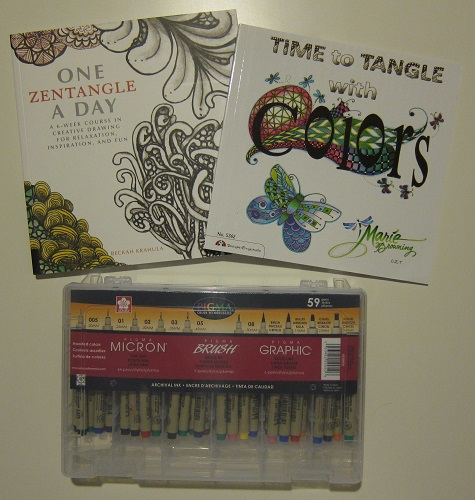 A large assortment of Sakura Pigma pens and two tangle books; One Zentangle a Day by Beckah Krahula and Time to Tangle with Color by Marie Browning.